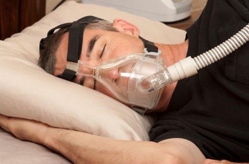 Patient présentant des apnées du sommeil et dormant avec un dispositif à PPC (illustration).