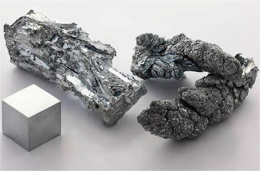 Zinc : à gauche, un fragment cristallin de lingot, à droite, des dendrites obtenues par sublimation-condensation, devant, un cube d'un cm de côté pour comparaison (illustration @Alchemist-hp sur Wikimedia).