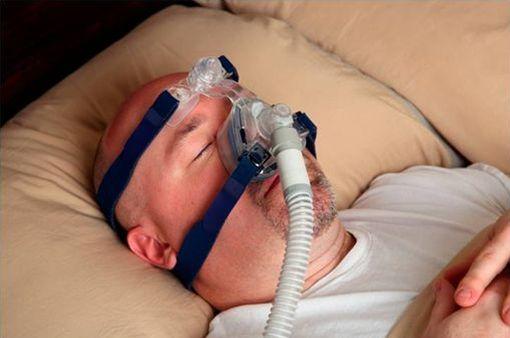 Patient souffrant d'apnées du sommeil et  dormant avec un dispositif à PPC (illustration).